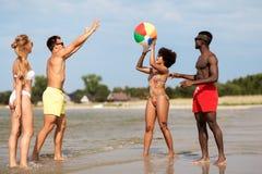 Vrienden die met strandbal spelen in de zomer stock afbeeldingen