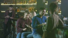 Vrienden die met telefoons bij barteller communiceren stock footage