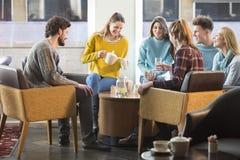 Vrienden die middagthee in een koffie hebben Stock Afbeeldingen