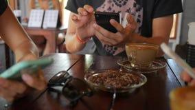 Vrienden die Mobiele Smartphones-Zitting in Koffiewinkel gebruiken thailand stock footage