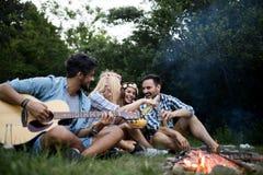 Vrienden die muziek spelen en van vuur in aard genieten stock fotografie