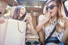 Vrienden die nieuwe aankoop na het winkelen bekijken stock fotografie