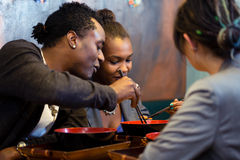 Vrienden die noedelsoep in Japans Restaurant eten stock foto's
