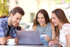 Vrienden die online met een creditcard en laptop winkelen Stock Afbeeldingen