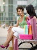 Vrienden die op bank met het winkelen zakken zitten royalty-vrije stock foto