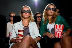 Vrienden die op 3D film letten bij bioskoop Stock Afbeeldingen