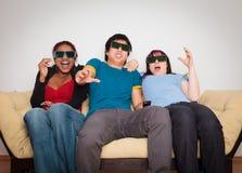 Vrienden die op 3d TV letten Stock Afbeeldingen