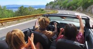 Vrienden die op de autosnelweg in rode convertibel drijven en op het overzees wijzen stock videobeelden