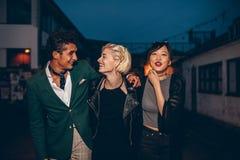 Vrienden die op de straat bij nacht lopen Royalty-vrije Stock Foto