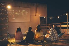 Vrienden die op een film op een terras van het de bouwdak letten royalty-vrije stock fotografie
