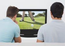 Vrienden die op golf op televisie thuis letten stock foto