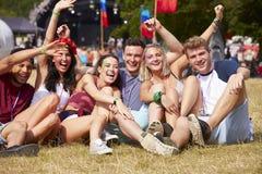 Vrienden die op het gras zitten die bij een muziekfestival toejuichen stock fotografie