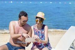 Vrienden die op het strand zitten, die pret met tabletten hebben Stock Afbeeldingen