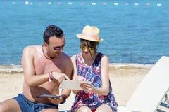 Vrienden die op het strand zitten, die pret met tabletten hebben Royalty-vrije Stock Foto's