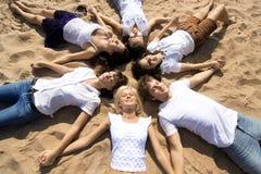 Vrienden, die op het zand liggen Royalty-vrije Stock Fotografie