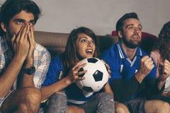 Vrienden die op voetbal letten stock foto's