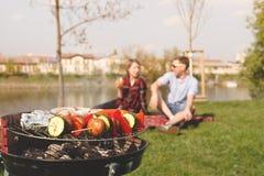 Vrienden die openluchtbarbecue hebben Grill met diverse barbecue, selectieve nadruk Royalty-vrije Stock Foto's