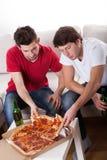 Vrienden die pizza eten Stock Foto's