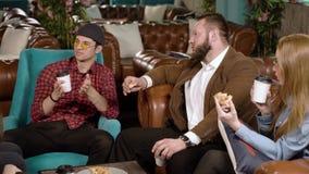 Vrienden die pizza eten en in de koffie babbelen stock videobeelden