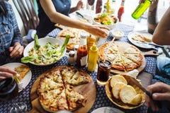 Vrienden die pizza hebben bij een restaurant Stock Afbeeldingen