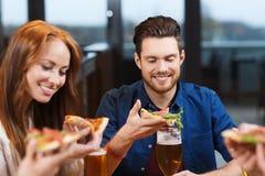 Vrienden die pizza met bier eten bij restaurant Stock Afbeeldingen