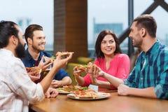 Vrienden die pizza met bier eten bij restaurant Stock Foto