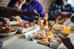 Vrienden die pizza samen thuis eten stock fotografie