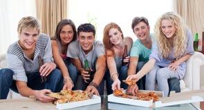 Vrienden die pizza thuis eten Stock Afbeeldingen