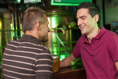 Vrienden die pret hebben bij bar. Twee vrolijke mannelijke vrienden die spreken bij Royalty-vrije Stock Foto