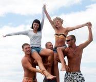 Vrienden die pret hebben bij het strand Stock Foto