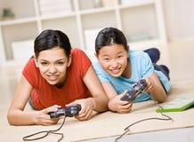 Vrienden die pret hebben die videospelletjecontrolemechanismen met behulp van Royalty-vrije Stock Afbeelding