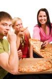 Vrienden die pret hebben en pizza eten Stock Afbeelding