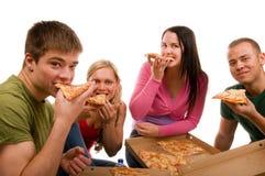 Vrienden die pret hebben en pizza eten Stock Foto's