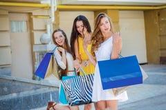 Vrienden die pret hebben samen Meisjes die het winkelen zakken houden en wal Stock Foto
