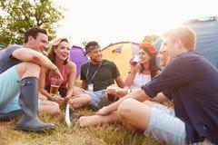 Vrienden die pret op het kampeerterrein hebben bij een muziekfestival stock foto's