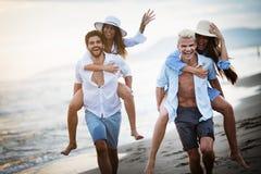 Vrienden die pret op het strand hebben onder zonsondergangzonlicht royalty-vrije stock fotografie