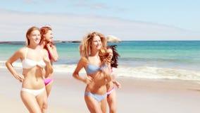 Vrienden die samen op het strand lopen stock videobeelden