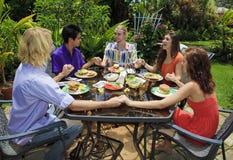 Vrienden die samen voor de lunch bidden stock fotografie