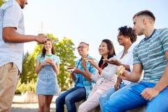Vrienden die sandwiches of burgers in park eten stock fotografie