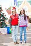 Vrienden die Santa Hat Standing In Courtyard dragen stock afbeelding