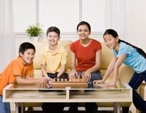 Vrienden die schaak verzamelen zich te spelen Stock Foto