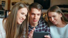 Vrienden die smartphones zitting in de koffie gebruiken stock footage