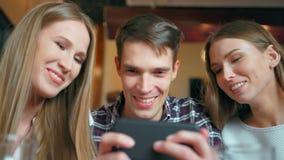 Vrienden die smartphones zitting in de koffie gebruiken stock video