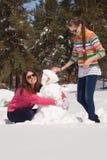 Vrienden die sneeuwman bouwen stock afbeelding