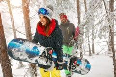 Vrienden die snowboarder door in het bos van de mistwinter gaan Stock Fotografie