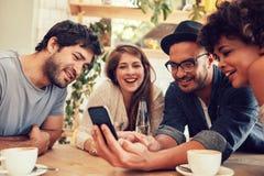 Vrienden die sommige foto's op mobiele telefoon delen stock foto