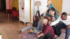 Vrienden die sport op spel op TV letten stock video