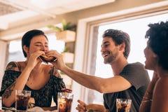 Vrienden die stapelhamburger hebben bij koffie Royalty-vrije Stock Afbeeldingen