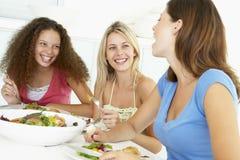 Vrienden die thuis het Hebben van Lunch ontspannen Stock Foto's