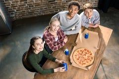 Vrienden die tijd samen met pizza en sodadranken doorbrengen, die pizza thuis concept eten Stock Foto's